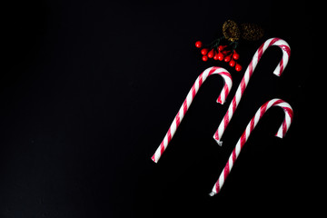 Candy canes on black background, Christmas table top view, red colours.
