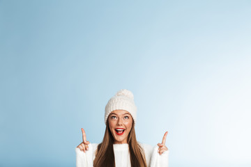 Beautiful cute amazing young woman posing isolated over blue wall background showing copyspace.