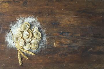 Italian ravioli, dumplings with meat on dark wooden old surface