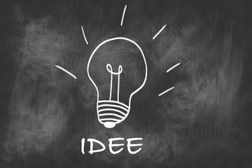 """Skizze einer Glühbirne auf einer Tafel als Konzept für """"Idee""""."""