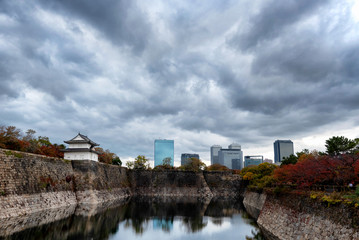Scene at the Osaka Castle grounds on a cloudy day in Osaka, Japan with modern buildings in the background