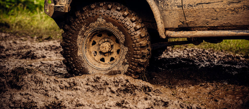 Getting off the beaten path. Car wheels on steppe terrain splashing with dirt. SUV or offroader on mud road. Car racing offroad. Offroad car in action. Dirty car drive on high speed