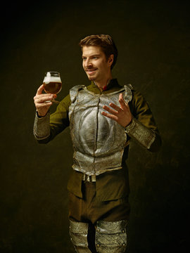 Medieval smiling happy knight with beer on dark studio background. Portrait in low key of brutal man in tradishional retro costume of spanish hidalgo. Human emotions, comparison of eras concept