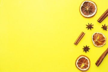Christmas background of dried oranges, star anise and cinnamon. Yellow background. Flat lay