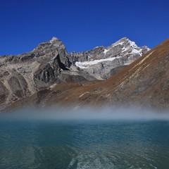 Morning fog over turquoise Lake Gokyo, Nepal.