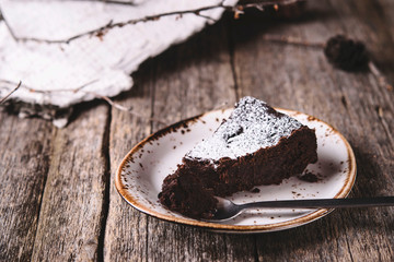 Kladdkaka. Traditional Swedish moist chocolate cake on old rustic wooden table decorated dry twigs, pine cones and birch bark. Fika. Hygge. Toned image
