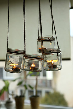 Aromatic candles in glass jars hanging in kitchen. DIY candles in glass jars hanging on linen jute.