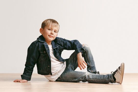 The portrait of cute little kid boy in stylish jeans clothes looking at camera against white studio wall. Kids fashion concept