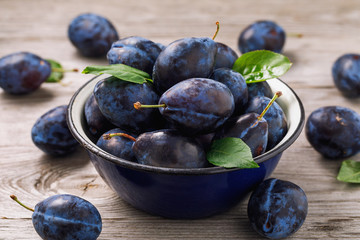 Full bowl of freshly harvested ripe prune fruits on wooden table closeup