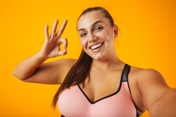 480e4bf0d1 Portrait of cheerful chubby woman in sportive bra using mobile phone for  selfie photo