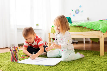 childhood, leisure and people concept - happy kids drawing at home
