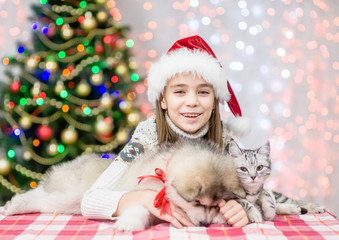 Happy little girl in red santa hat embracing puppy and kitten on a background of the Christmas tree