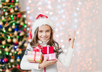 Smiling girl holding many gift boxes and pointing away. Empty space for text