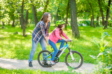 Happy family. Smiling mom teaches her daughter to ride a bicycle in the park