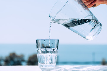 Pure water from a jug is poured into a glass beaker. Glass with water on the background of the sea.