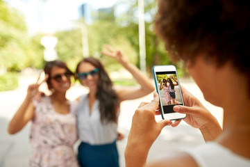 female friendship, technology and people - woman with smartphone photographing her friends showing peace hand sign in summer park