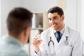 medicine, healthcare and people concept - smiling doctor showing jar with drug to male patient at medical office in hospital