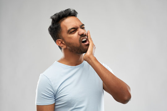 people, dentistry and health problem concept - indian man suffering from toothache over grey background
