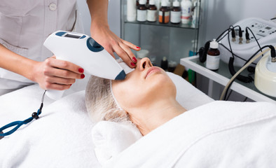 Aged woman making procedures for face in spa salon
