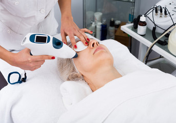 Aged woman making beauty procedures for face in spa salon