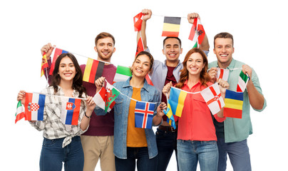 international friendship and people concept - group of smiling friends with flags of different...