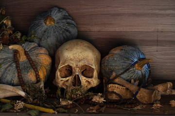 Skull with bone and thai pumpkins whis has old beads put on old wooden table which has dim light