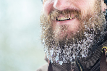 Beard in icicles. Part of the face of a smiling young man in a brown sports jacket. Concept of winter sports in the open air.
