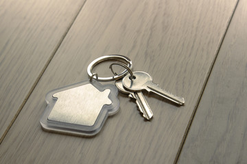 Keys with keychain - house close-up on a wooden table.