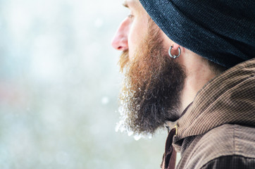 Beard covered with icicles and frozen droplets. Young man winter portrait in profile.