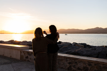 Two women photographing sunset