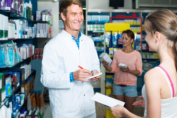 portrait of man druggist in white coat giving advice to customers in pharmacy