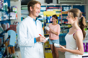 Cheerful pharmacist helping customers