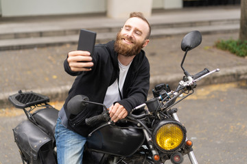 Portrait of happy young biker taking selfie on motorcycle. Caucasian bearded man photographing himself with smartphone outdoors. Biker culture concept
