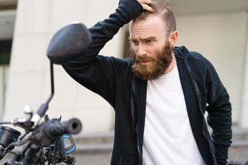 Portrait of troubled young bearded man standing at motorcycle. Caucasian biker standing at his broken motorbike. Vehicle breakdown concept