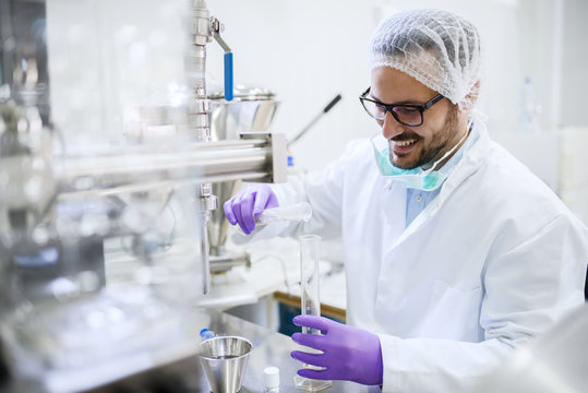 Smiling chemist pouring water into the test tube while standing in the lab. Water quality check concept.
