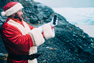 Santa Claus pointing his mobile phone