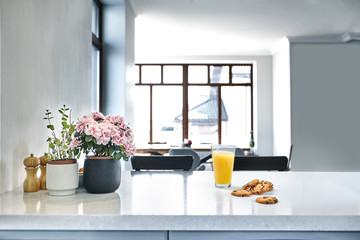 Appetizing sweet orange juice and one drinking glasses standing on a white table in the kitchen for a breakfast.