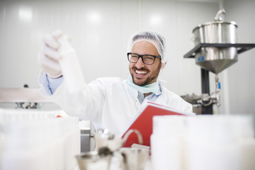 Smiling scientist holding bottle with creme in one hand and test results in other hand while sitting in the lab.