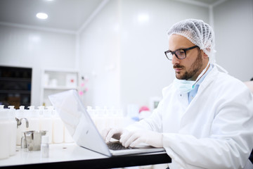 Scientist using laptop for entering test results while sitting in the lab. On desk cosmetic products.