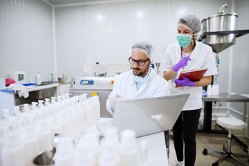 Scientist doing research in cosmetic factory. Next to him assistant with folder in hands. On the desk bottles and laptop.