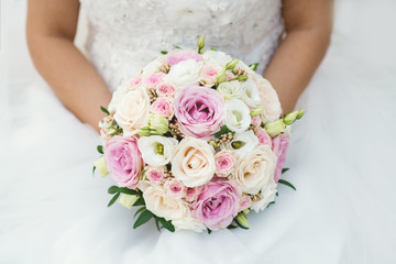 Beautiful bride in a wedding dress holding a bouquet of pink roses. White background. Text space.