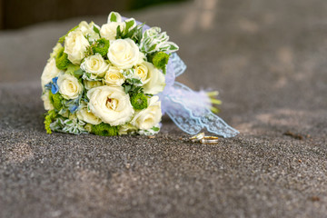bridal bouquet of yellow roses and wedding rings over gray stone - close up