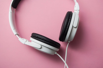closeup of white headphones on pink background
