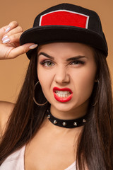 Hip-hop girl in cap with long dark hair. Fashion portrait of modern young woman in cap