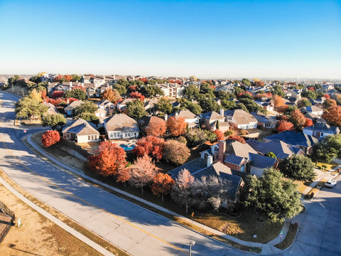 Top view planned unit development suburbs of Dallas, Texas, USA in autumn season. Picture from drone residential area with colorful fall foliage leaves under blue sky