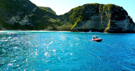 Covered Boat Cruising Off Karang Dawa Ocean Cliffs - Nusa Penida, Indonesia