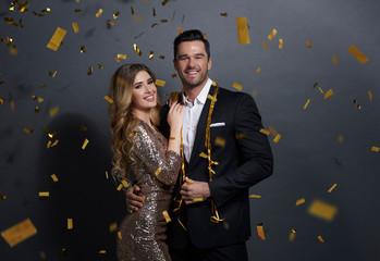 Portrait of embraced couple celebrating New Year at studio shot