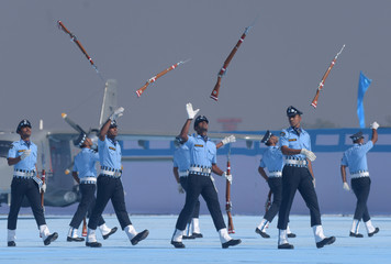 IAF soldiers toss their rifles as they perform during the presentation of President's Standards and Colours to 118 Helicopter Unit and the Air Defence College at Air Force Station in Guwahati