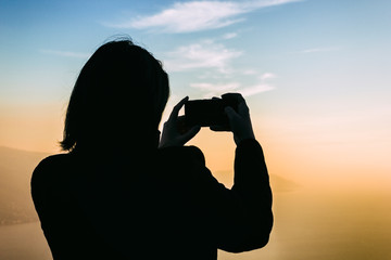 Silhouette of a tourist girl taking picture with a smartphone