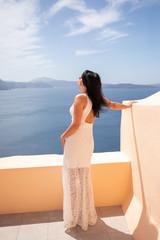Schöne Frau im weißen Kleid schaut in Santorini auf dem Meer